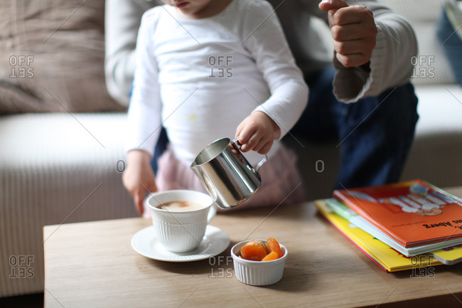 Small girl pouring milk from jug into cup of coffee