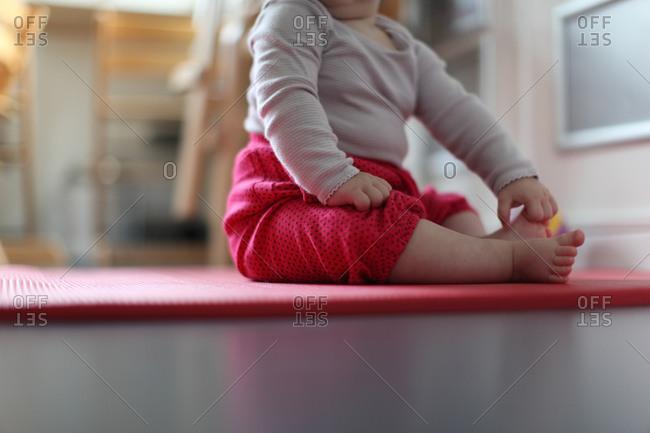 Baby girl sitting on red floor mat in kindergarten