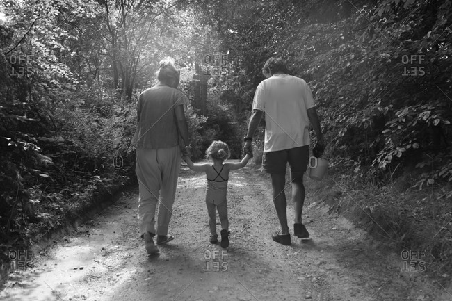 Woman and man walking on path with child