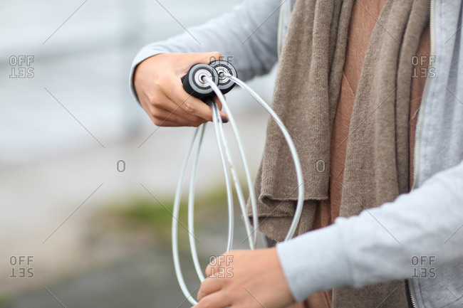 Young woman rolling up skipping rope