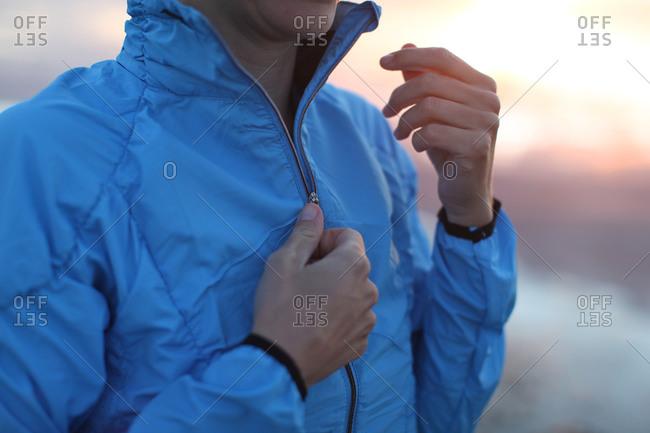Woman zipping up blue training jacket