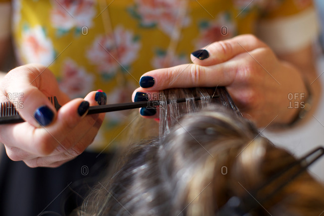 Hairdresser adjusting woman's hair for highlights