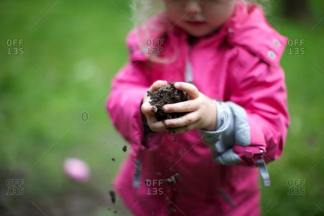 Girl trying to make mud ball