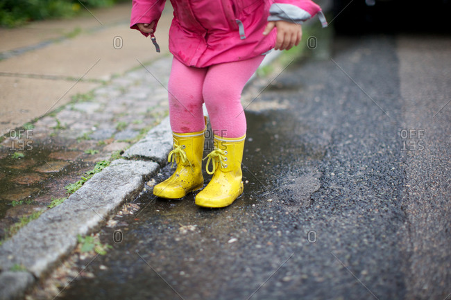 A girl in rain boots at roadside