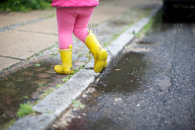 A girl in rain clothes at roadside