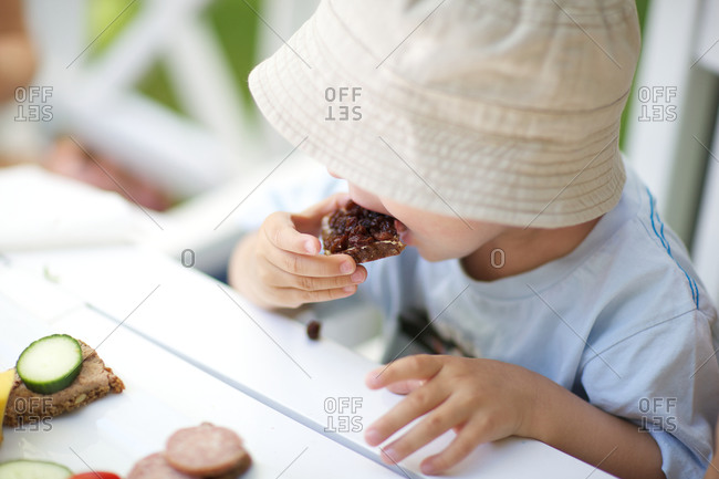 Little boy eating rye bread with meat