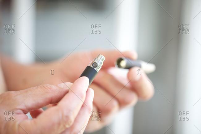Hands holding e-cigarette pieces