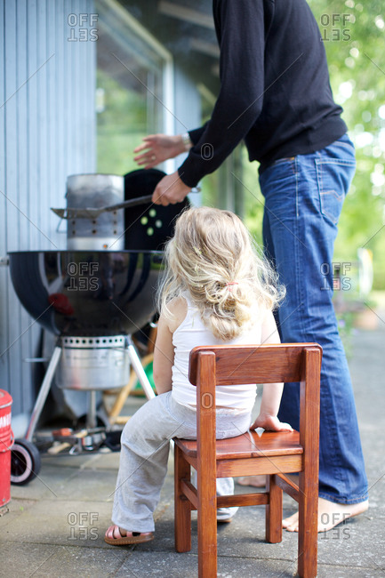 Little girl with father grilling out
