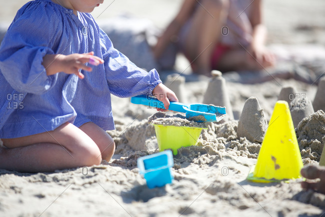 Girls playing with toys on sand