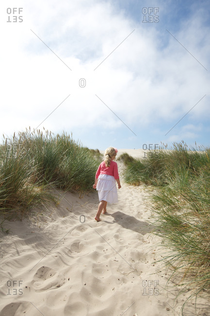 Rear view of girl walking alone on sand hill