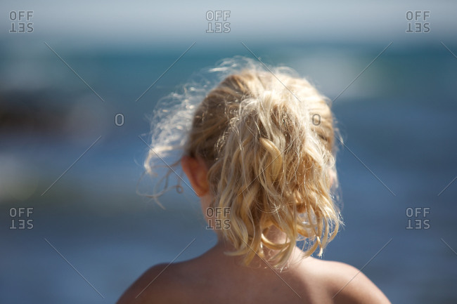 Rear view of little blond girl at the sea