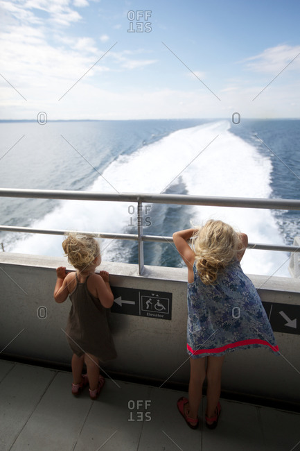 Girls looking at seascape from ship