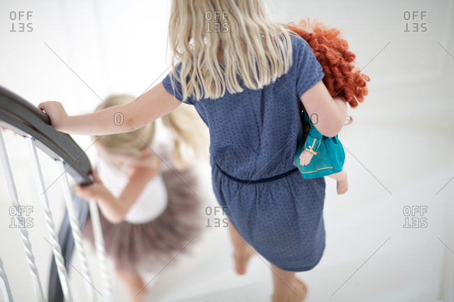 Girls walking downstairs with a doll