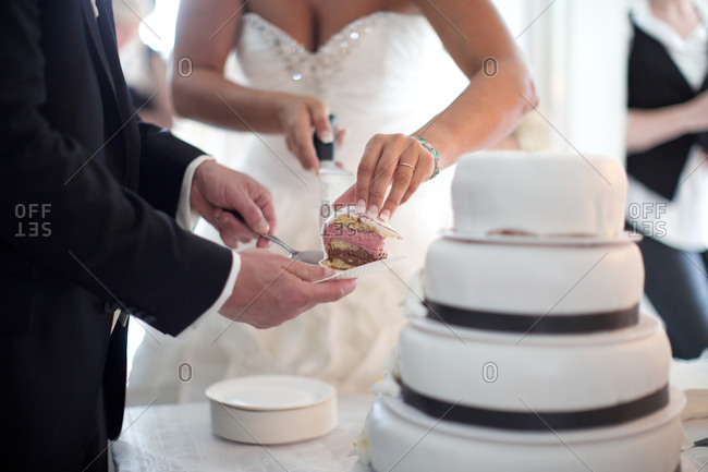 Groom with bride cutting the wedding cake