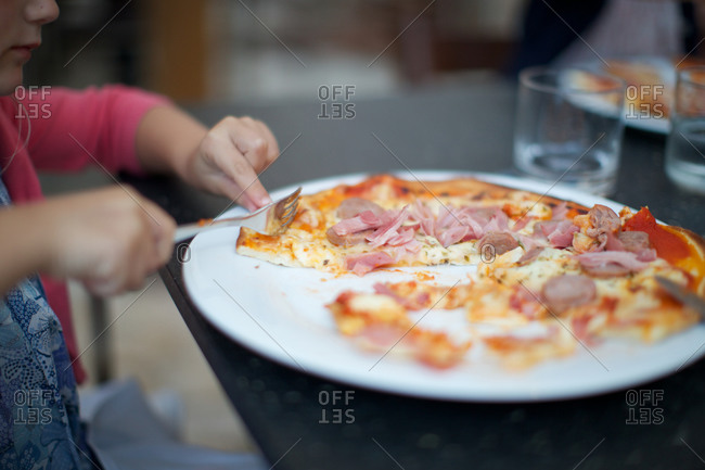 Little girl cutting bite of pizza