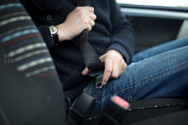 Man buckling seat belt in car