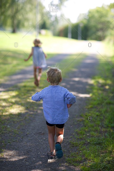 Rear view of children running at park
