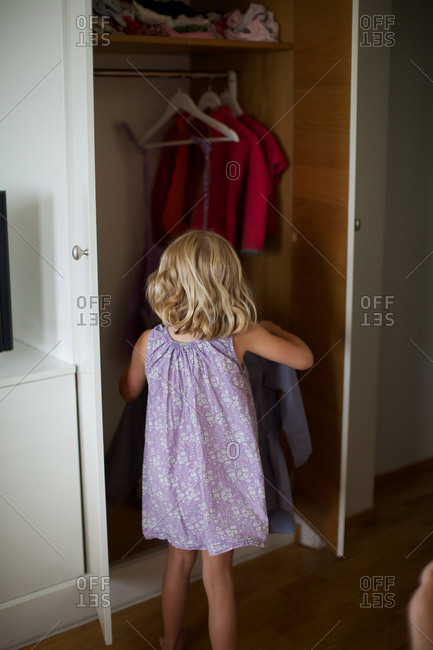 Rear view of girl removing clothes from wardrobe