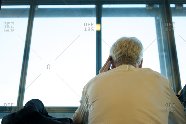 Rear view of old man talking on cell phone