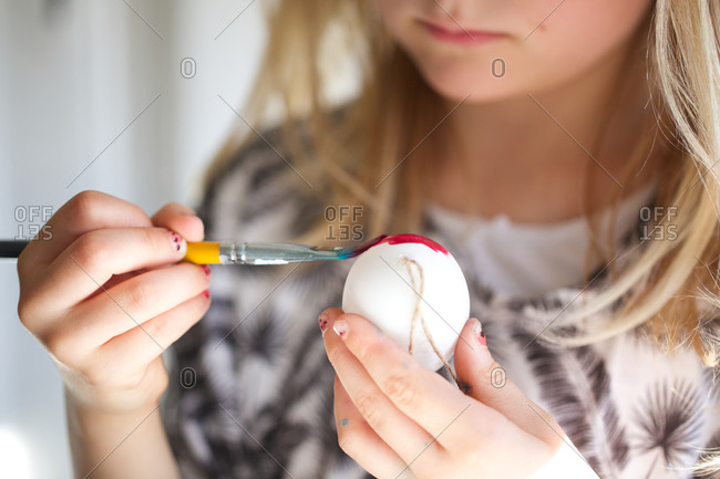 Girl painting Easter eggs with brush
