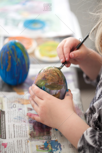 Girl painting eggs using brush