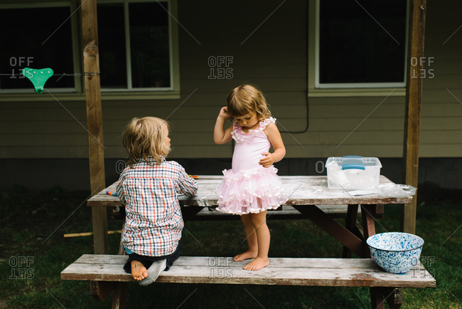 Brother and sister playing on a picnic table