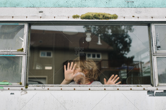 Boy at the window of an old camping trailer
