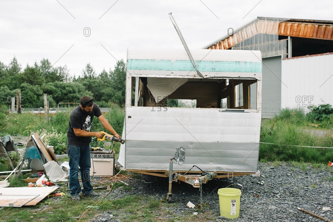 Man tearing apart an old camping trailer