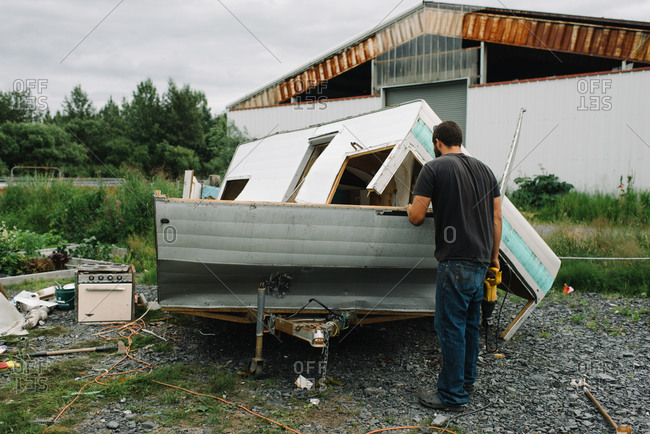 Man destroying an old camping trailer