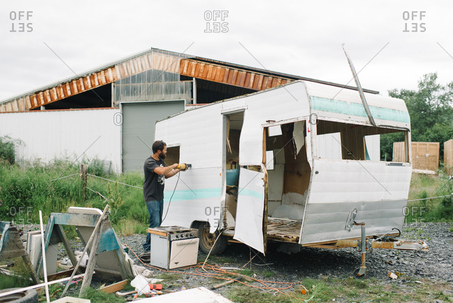 Man dismantling and old camping trailer