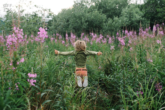 Boy leaping through tall wildflowers