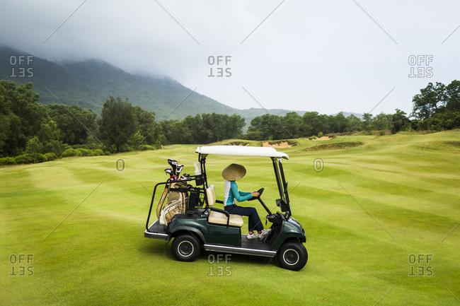 Lang Co, Vietnam - March 25, 2015: A caddie drives a golf cart on a Vietnamese golf course
