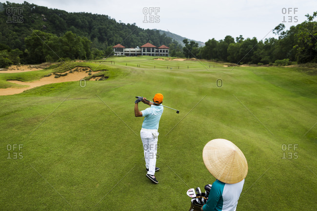 Lang Co, Vietnam - March 25, 2015: A golfer and caddie at a Vietnamese golf course