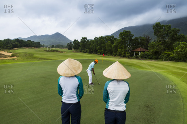 Lang Co, Vietnam - March 25, 2015: Two caddies watch a golfer putt at a Vietnamese golf course