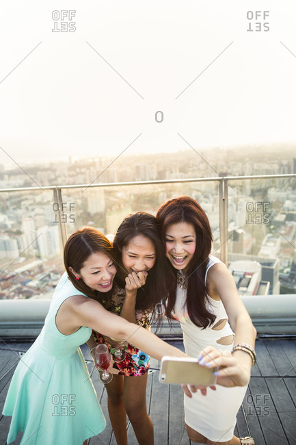 Singapore - March 7, 2015: Three young women at a rooftop bar in downtown Singapore