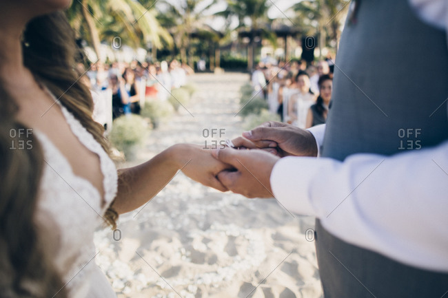 A husband and wife exchange wedding rings at a small ceremony on a beach in Southeast Asia