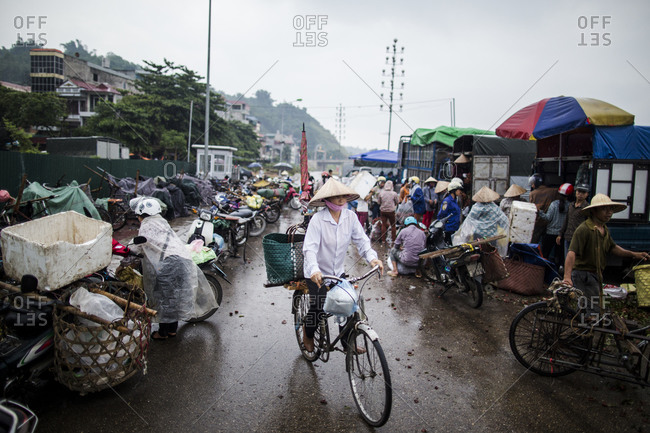 Lao Cai, Vietnam - June 22, 2015: A woman rides her bicycle through a morning market in Vietnam