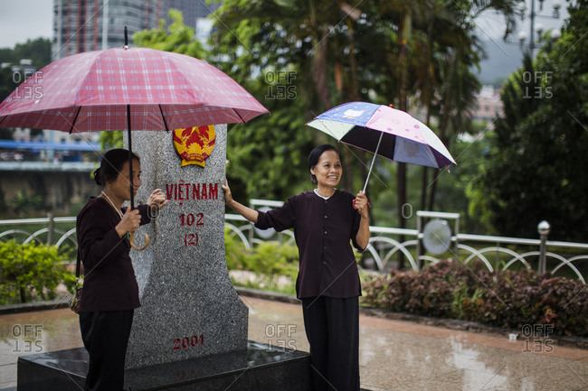 Lao Cai, Vietnam - June 22, 2015: Vietnamese women pose for a portrait near a Vietnamese border marker, with a view of China behind them