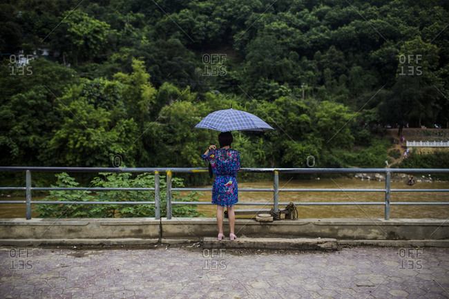 A woman waits for friends and family at a small illegal border crossing just outside of downtown Lao Cai, Vietnam