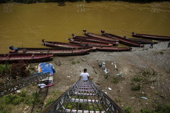 A man slides down a ladder towards boats at a small illegal border crossing just outside of downtown Lao Cai, Vietnam into China