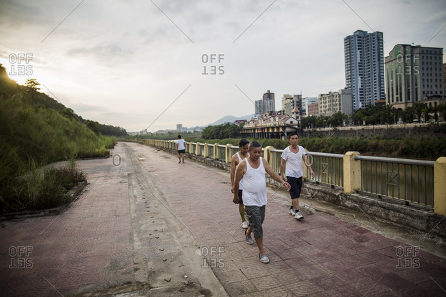 Lao Cai, Vietnam - June 22, 2015: Vietnamese men walk along a river promenade in the late afternoon in Lao Cai, Vietnam, with China just on the other side of the river