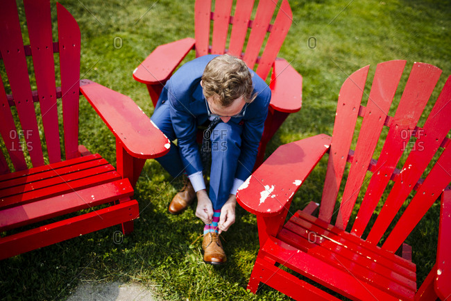 A man ties his shoes on a red lawn chair before his wedding along the coast in Nova Scotia, Canada