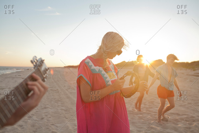 Young woman playing tambourine on beach with friends at sunset