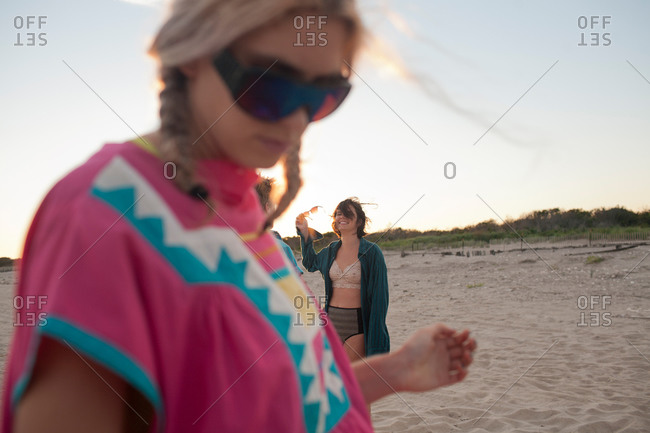 Two women hanging out on the beach together at dusk