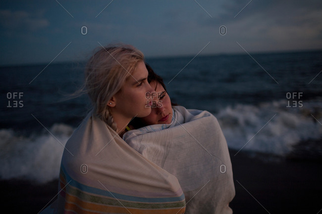 Two women wrapped in a blanket together on beach at night