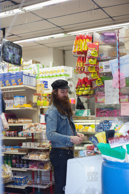 Bearded man making a purchase at a bodega