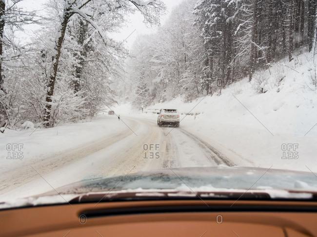 Cars on road in winter landscape