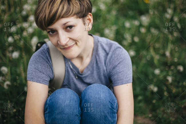 Portrait of smiling young woman sitting on a meadow