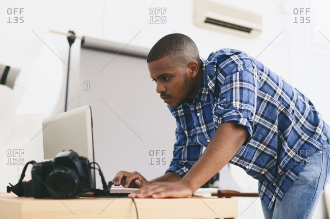 Young man working with laptop in his photographic studio