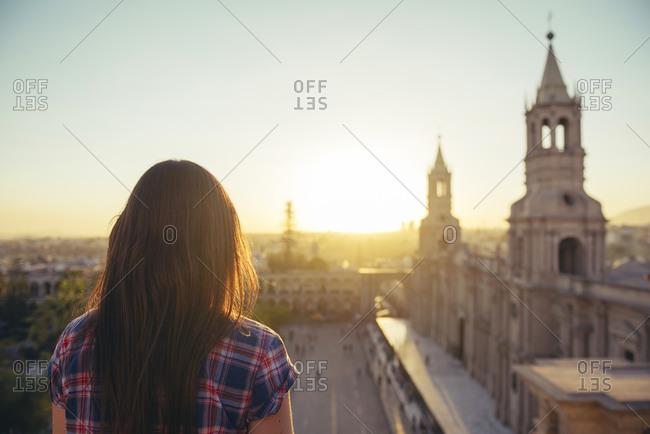Woman looking at Plaza de Armas enjoying sunset, Arequipa